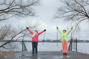 Senior women in autumn park have training - warm up before nordic walking