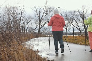 Healthy lifestyle for elderly women - nordic walking in autumn park, rear view