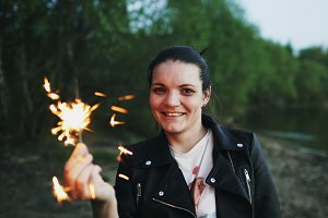 Portrait of young smiling woman with sparkler celebrating at beach party