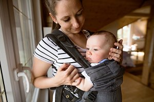 Beautiful mother with her cute little son in baby carrier