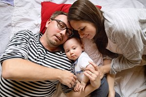 Beautiful young family with little son lying on bed.