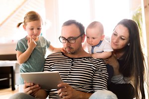Young parents with little children and tablet at home.