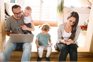 Young parents with little children and gadgets at home.