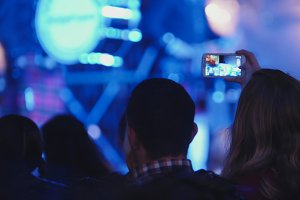 Spectators at concert - people shooting performance on smartphone, scottish musicians
