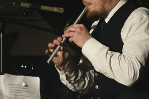 Bearded man plays pipe on the stage