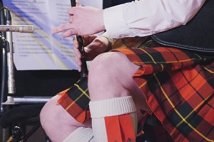 Bearded man in the kilt plays pipe on the stage
