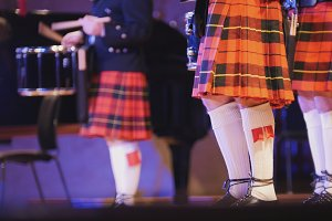 Traditional scottish band musicians singing with bagpipes on the stage during concert