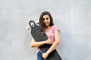 Beautiful teenage student with skateboard against concrete wall.