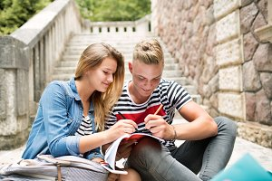 Attractive teenage student couple in front of university studyin