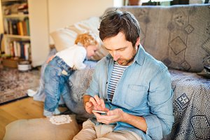 Young father with smartphone at home with his little son.