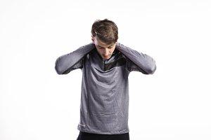 Fit man in gray sweatshirt stretching arms, studio shot.