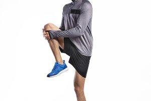 Fit man in gray sweatshirt stretching legs, studio shot.