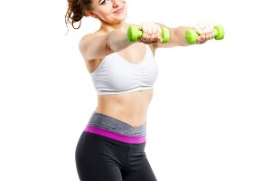 Young sporty woman doing exercises with dumbbells