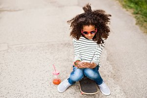 Beautiful african american girl with smartphone and skateboard.