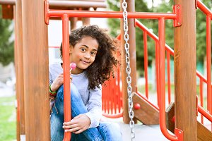 African american girl on playground eating lollipop.
