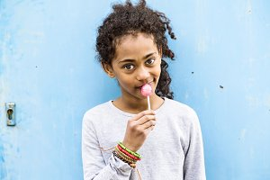 African american girl with curly hair outdoors eating lollipop.