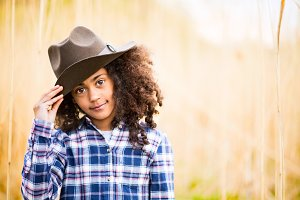 African american girl in checked shirt outdoors in field.