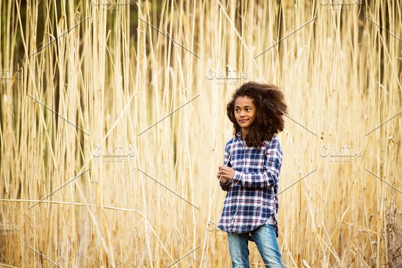 African American Girl In Checked Shirt Outdoors In Field