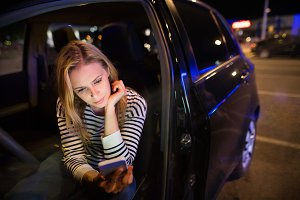 Woman with smartphone in her car at night.