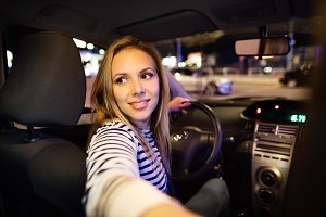 Beautiful young woman driving her car at night.
