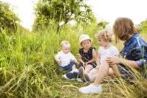 Cute little children outside in in green summer nature.