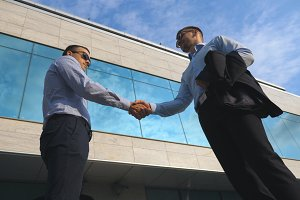 Two young businessmen meeting near office and greeting each other. Business man passing a black briefcase to his partner. Colleagues shake hands outdoor in the city background. Close up Slow motion