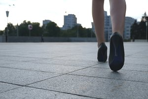 Follow to female legs in high heels shoes walking in the urban street. Feet of young business woman in high-heeled footwear going in the city. Girl stepping to work. Slow motion Closeup Rear back view