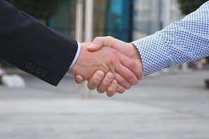 Colleagues meet and shake hands in the city background. Two businessmen greeting each other in urban environment. Business handshake outdoor. Shaking of male arms outside. Close up Slow motion