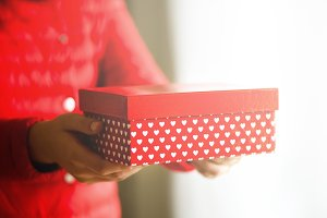 Female hands holding red gift box with white hearts, copy space. Christmas, hew year, birthday, valentines day concept. Banner