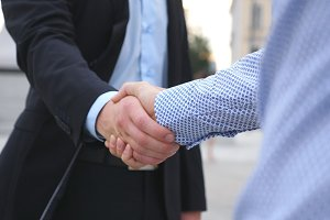 Business handshake with blurred city background. Two businessmen greeting each other in urban environment. Shaking of male arms outside. Colleagues meet and shake hands outdoor. Close up Slow motion