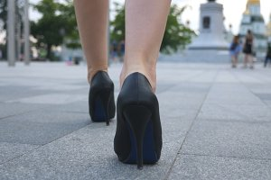 Follow to female legs in high heels shoes walking in urban street. Feet of young business woman in high-heeled footwear going in the city. Girl stepping to work. Slow motion Close up Rear back view