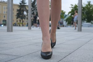 Feet of young business woman in high-heeled footwear going in the city. Female legs in high heels shoes walking in the urban street. Girl stepping to work. Slow motion Close up Front view