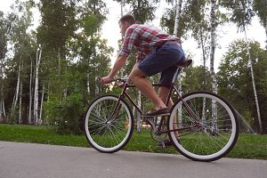 Follow to young handsome man riding a vintage bicycle outdoor. Sporty guy cycling at the park. Healthy active lifestyle. Side view Close up Slow motion