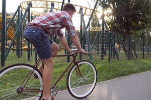 Young handsome man riding a vintage bicycle at amusement park. Sporty guy cycling outdoor. Sun shine at background. Healthy active lifestyle. Close up Slow motion