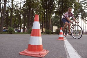 Cyclist go round traffic cones. Young handsome man riding a vintage bicycle. Sporty guy cycling at the park. Healthy active lifestyle. Low angle of view Close up Slow motion
