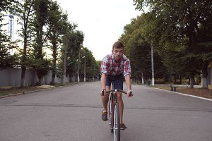 Portrait of young handsome man riding a vintage bicycle at park road. Sporty guy cycling outdoor. Healthy active lifestyle. Front view Close up Slow motion