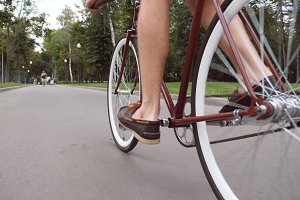 Young man riding a vintage bicycle at the park road. Sporty guy cycling outdoor. Healthy active lifestyle. Low angle of view Close up Slow motion