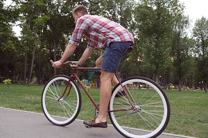 Sporty guy cycling at the park road. Young handsome man riding a vintage bicycle outdoor. Healthy active lifestyle. Side view Close up Slow motion