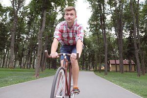 Portrait of young happy man riding a vintage bicycle at the park road. Sporty guy cycling outdoor and smile. Healthy active lifestyle. Front view Close up Slow motion