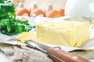 A bar of butter is cut into pieces on a wooden board with a knife, surrounded by milk, eggs and parsley on a white table. Ingredients for cooking.