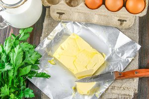 A bar of butter is cut into pieces on a wooden board with a knife, surrounded by milk, eggs and parsley on a brown table. Ingredients for cooking.