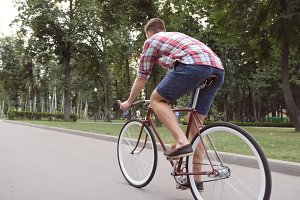 Young man riding vintage bicycle at the park alley. Sporty guy cycling outdoor. Healthy active lifestyle. Rear Back view Close up Slow motion