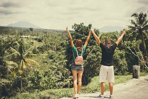 Happy young romantic couple looking at Batur volcano on a tropical island of Bali, Indonesia.