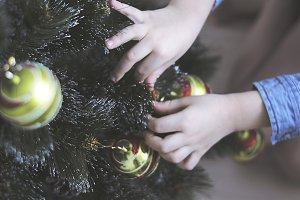 child decorates a Christmas tree