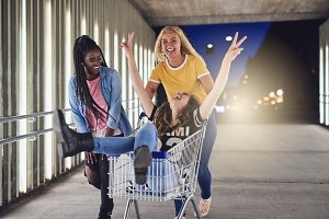 Young female friends playing with a shopping cart at night