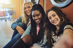 Diverse young female friends taking selfies together in a laundromat