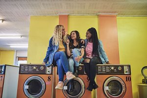 Young friends sitting on washing machines laughing and chewing gum