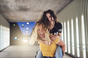 Laughing woman piggybacking her friend in the city at night