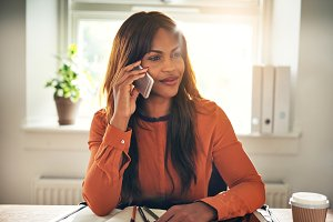 Smiling entrepreneur talking on a cellphone in her home office