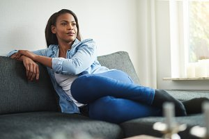 Content young African woman relaxing on her sofa at home
